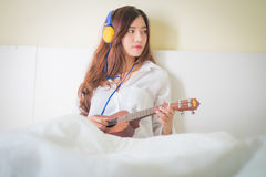 Señora joven que juega el ukelele en su dormitorio Imágenes de archivo libres de regalías
