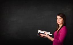 Señora joven que lee un libro Foto de archivo