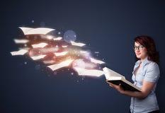 Señora joven que lee un libro con las hojas de vuelo que salen del b Fotografía de archivo libre de regalías