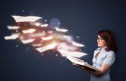 Señora joven que lee un libro con las hojas de vuelo que salen del b Imagen de archivo libre de regalías
