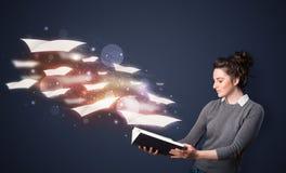 Señora joven que lee un libro con las hojas de vuelo que salen del b Foto de archivo