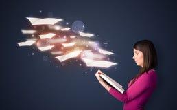 Señora joven que lee un libro con las hojas de vuelo que salen del b Foto de archivo libre de regalías