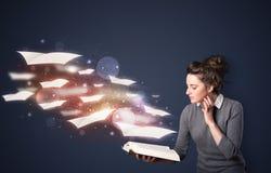 Señora joven que lee un libro con las hojas de vuelo que salen del b Imagen de archivo
