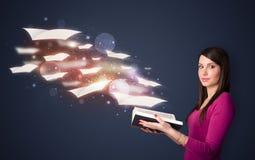 Señora joven que lee un libro con las hojas de vuelo que salen del b Fotografía de archivo