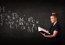 Señora joven que lee un libro con las letras del alfabeto Imágenes de archivo libres de regalías