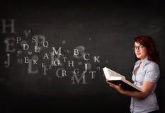 Señora joven que lee un libro con las letras del alfabeto Imagenes de archivo