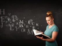 Señora joven que lee un libro con las letras del alfabeto Fotos de archivo