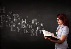 Señora joven que lee un libro con las letras del alfabeto Foto de archivo libre de regalías
