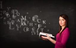 Señora joven que lee un libro con las letras del alfabeto Fotografía de archivo libre de regalías