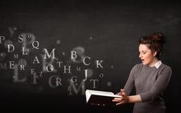 Señora joven que lee un libro con las letras del alfabeto Fotos de archivo libres de regalías