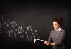 Señora joven que lee un libro con las letras del alfabeto Imagen de archivo