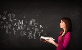 Señora joven que lee un libro con las letras del alfabeto Fotografía de archivo