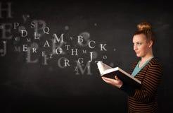 Señora joven que lee un libro con las letras del alfabeto Imagen de archivo libre de regalías