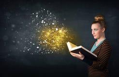 Señora joven que lee un libro mágico Imagen de archivo libre de regalías