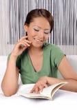 Señora joven que lee un libro mientras que miente en cama Imágenes de archivo libres de regalías