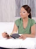 Señora joven que lee un libro mientras que miente en cama Foto de archivo
