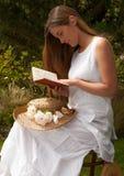 Señora joven que lee una sentada del libro fotografía de archivo