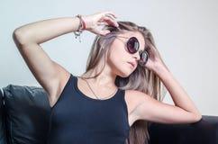 Señora joven que lleva las gafas de sol redondeadas Foto de archivo libre de regalías