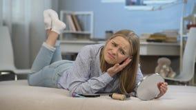 Señora joven que miente en la cama, preocupante sobre sus problemas de piel, cambios relativos a la edad almacen de video