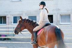 Señora joven que monta un lomo de caballo en la granja ecuestre Fotografía de archivo libre de regalías