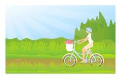 Señora joven que monta una bici Fotos de archivo libres de regalías