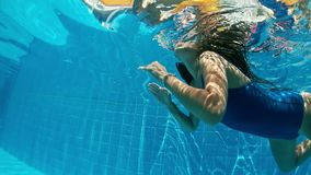 Señora joven que nada bajo el agua en la piscina Retrato subacuático de la mujer en piscina metrajes
