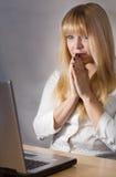 Señora joven que parece preocupada delante de su ordenador Foto de archivo libre de regalías