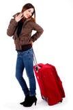 Señora joven que presenta con equipaje Fotografía de archivo