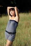 Señora joven que presenta en un prado Imágenes de archivo libres de regalías