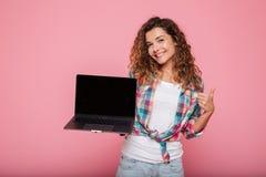 Señora joven que señala en el espacio de la copia en el ordenador portátil aislado sobre rosa Fotos de archivo libres de regalías