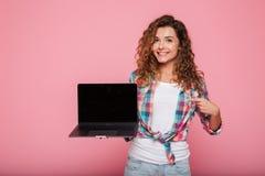 Señora joven que señala en el espacio de la copia en el ordenador portátil aislado sobre rosa Imágenes de archivo libres de regalías