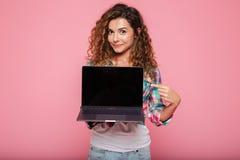 Señora joven que señala en el espacio de la copia en el ordenador portátil aislado sobre rosa Imagenes de archivo