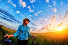 Señora joven que se coloca con la bicicleta en un prado en la puesta del sol Fotografía de archivo libre de regalías