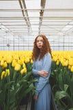 Señora joven que se coloca entre las flores Foto de archivo