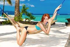 Señora joven que se relaja en hamaca en la playa tropical fotografía de archivo libre de regalías