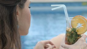 Señora joven que se relaja por el cóctel que sorbe de la piscina y que disfruta de viaje de las vacaciones de verano almacen de video
