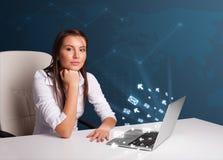 Señora joven que se sienta en el dest y que pulsa en la computadora portátil con ico del mensaje Imagen de archivo libre de regalías
