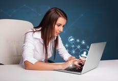 Señora joven que se sienta en el escritorio y que pulsa en la computadora portátil con el netw social Fotos de archivo libres de regalías