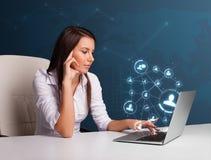 Señora joven que se sienta en el escritorio y que pulsa en la computadora portátil con el netw social Foto de archivo