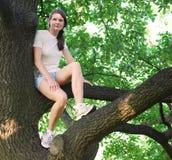 Señora joven que se sienta en el roble Imagen de archivo libre de regalías