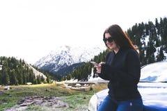 señora joven que se sienta en un capo de un coche usando el teléfono elegante en las montañas Muchacha feliz que envía el mensaje fotografía de archivo libre de regalías