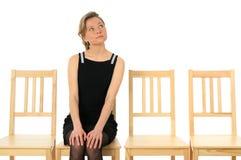 Señora joven que se sienta en una silla y esperar Foto de archivo
