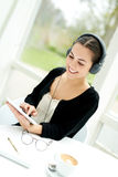 Señora joven que selecciona un tono de su biblioteca de música Foto de archivo libre de regalías