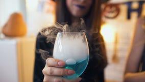 Señora joven que sonríe y que sostiene el cóctel azul con el humo blanco en el partido de Halloween almacen de metraje de vídeo
