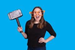 Señora joven que sostiene un apoyo de goma de la foto del martillo del mazo y un retrato anaranjado grande de la cabina de la fot foto de archivo libre de regalías