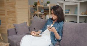 Señora joven que toma notas en el cuaderno que mira la pantalla del smartphone en casa metrajes