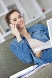 Señora joven que usa el ordenador portátil y hablando en el teléfono Fotos de archivo
