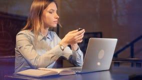Señora joven que usa el ordenador portátil y el smartphone tarde en la noche 4K almacen de metraje de vídeo
