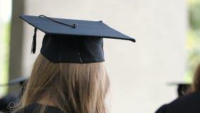 Señora joven rubia en ceremonia que concede de observación del casquillo académico en la universidad almacen de metraje de vídeo