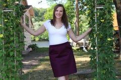Señora joven sonriente en el país en el río Imágenes de archivo libres de regalías